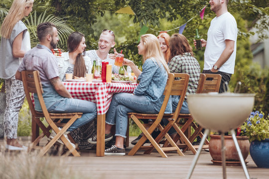 People gathered around a wooden table, eating, drinking and having fun during a grill party on the terrace.