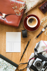 Top view on wooden desk with camera and cup of coffee next to red bag and postcard