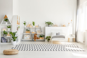 Scandinavian style, wooden furniture with plants and mountain decorations in a sunny, monochromatic child bedroom interior with white walls