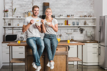 happy couple having breakfast and sitting on kitchen counter