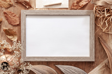 Blank mockup frame on an autumn desk with leaves, white flowers, old envelopes and dried decoration