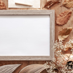A square photo of an empty mockup frame on an autumn desk with leaves, white flowers, old envelopes and dried decoration
