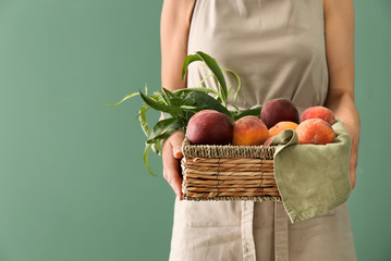 Woman holding basket with fresh peaches on color background