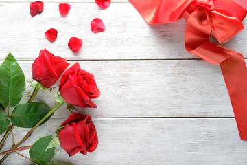 Beautiful red roses and gift box on white wooden background