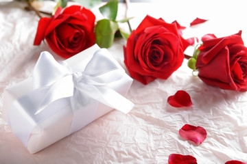 Beautiful red roses and gift box on packing paper