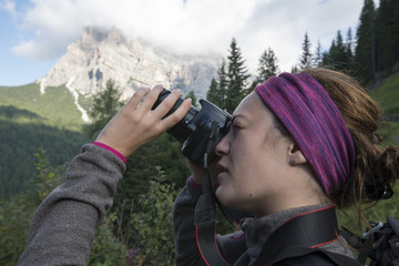 Young woman taking pictures of a mountain