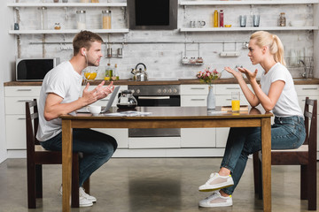 side view of emotional young couple quarreling during breakfast in kitchen