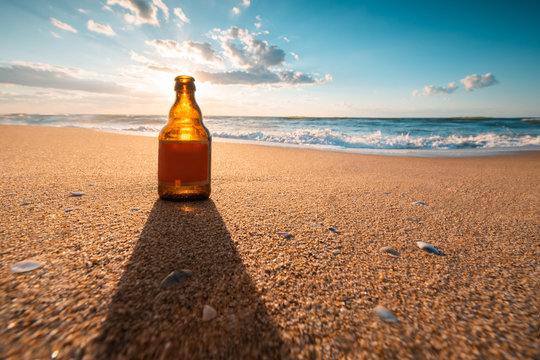 Beautiful sea sunrise and beer bottle on the beach sand