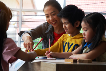 Teachers are teaching drawing on white paper to three children in holiday weekend.