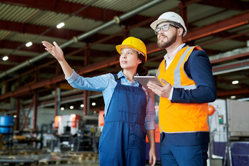 Low angle portrait of female factory worker giving tour of production workshop to businessman wearing hardhat and pointing away, copy space