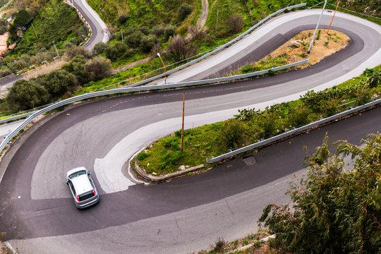 A car taking a sharp turn on a winding serpentine road near Savoca, Sicily, Italy