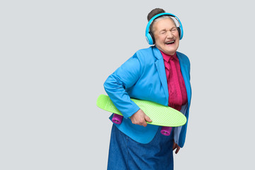 Trendy funny joyful grandmother in colorful casual style with blue headphones holding green skateboard listening music and laughing with closed eyes. indoor studio shot, isolated on gray background.