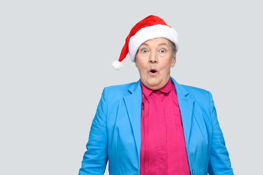 Surprised grandmother in colorful casual style with blue suit and christmas santa red cap standing and looking at camera with amazed face and open mouth and eyes. indoor, isolated on gray background