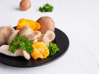 Champinon, Pfifferlinge und Petersilie auf einem schwarzen Teller auf einem weißen Tisch