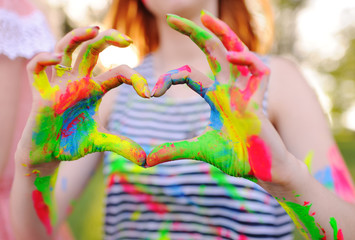 the girl with the hands smeared with colored fingers shows the heart on the background of nature and the sun