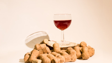 Empty glass of wine with wine stoppers (cork) inside on a white