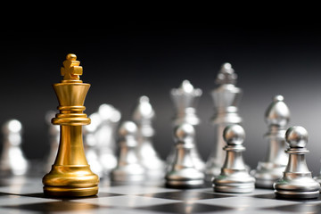 Gold king chess piece face with another silver team on black background (Concept for company strategy, business victory or decision)