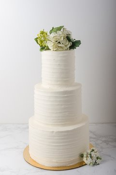 3 tier wedding cake with buttercream ruffles and edible flowers. On white background.