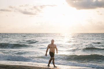 Strong old man walking on the beach