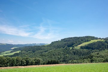 Color outdoor idyllic summer landscape with a fields,meadow,trees and forest under a clear blue bright sunny sky with some light clouds and a view over valleys towards the horizon