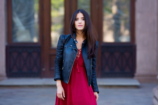 Autumn city fashion. Beautiful woman in red dress and black jacket. Urban background.