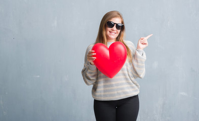Young adult woman over grey grunge wall holding red heart in love very happy pointing with hand and finger to the side
