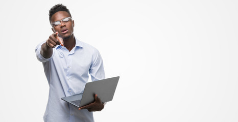 Young african american businessman using computer laptop pointing with finger to the camera and to you, hand sign, positive and confident gesture from the front