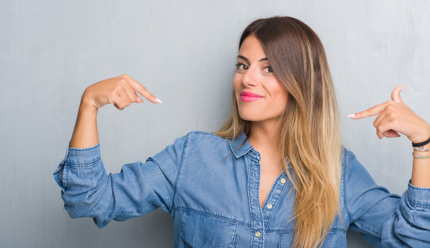 Young adult woman over grunge grey wall wearing denim outfit looking confident with smile on face, pointing oneself with fingers proud and happy.