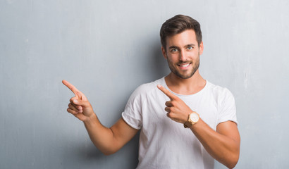 Handsome young man over grey grunge wall smiling and looking at the camera pointing with two hands and fingers to the side.