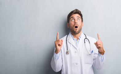 Handsome young doctor man over grey grunge wall amazed and surprised looking up and pointing with fingers and raised arms.