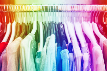 Colorful woman's clothes on black hangers in cloth's shop. Rainbow colored.