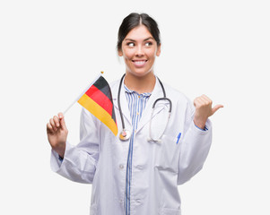 Young hispanic doctor woman holding flag of germany pointing and showing with thumb up to the side with happy face smiling