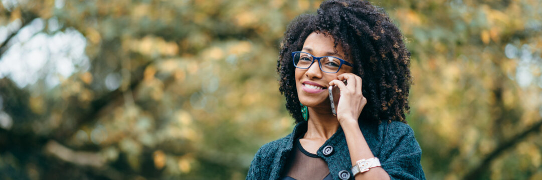 Happy black woman during a mobile phone call in autumn