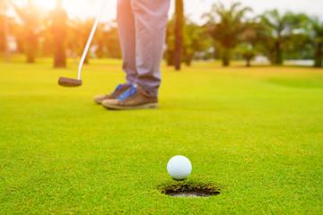 Golfer putting golf ball on the green golf, lens flare on sun set evening time, Pro Golf long putting golf ball in to the hole, sunset scene time.