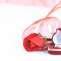 wedding rings and red rose on white background.photo with copy s