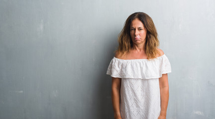 Middle age hispanic woman standing over grey grunge wall skeptic and nervous, frowning upset because of problem. Negative person.