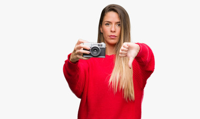 Beautiful young woman holding vintage camera with angry face, negative sign showing dislike with thumbs down, rejection concept