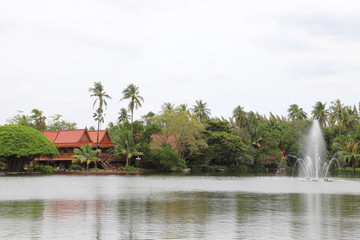 Scenery of beautiful Thai style houses in the garden nearby the lake with fountain.