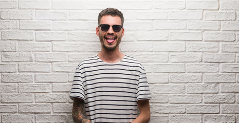 Young adult man wearing sunglasses standing over white brick wall sticking tongue out happy with funny expression. Emotion concept.