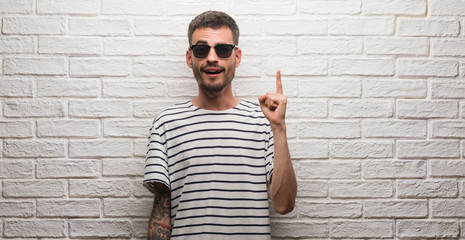 Young adult man wearing sunglasses standing over white brick wall pointing finger up with successful idea. Exited and happy. Number one.