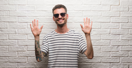 Young adult man wearing sunglasses standing over white brick wall showing and pointing up with fingers number ten while smiling confident and happy.