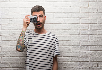 Young man holding vintage camera standing over white brick wall scared in shock with a surprise face, afraid and excited with fear expression