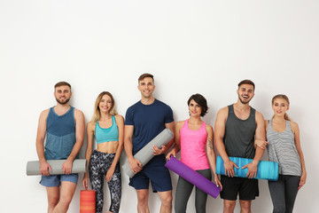 Group of young people waiting for yoga class on light background