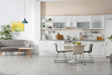 Stylish apartment interior with kitchen furniture and sofa