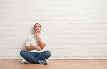 Young caucasian man sitting on the floor over white brick wall with hand on chin thinking about...