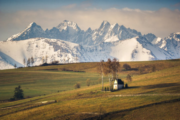 Landscape with a chapel and snow-covered Tatra Mountains in Kacwin, Malopolskie, Poland