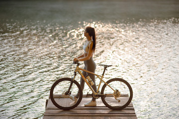 Side view of beautiful brunette woman in stylish sportswear with bicycle standing on the pier near the lake and green forest on the background.