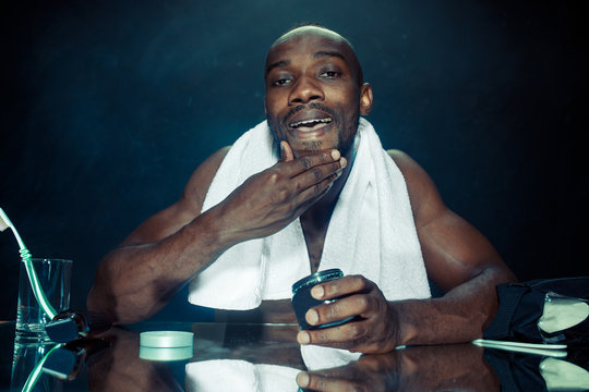 The young african man in bedroom sitting in front of the mirror after scratching his beard at home. Human emotions concept. after shave cream concepts