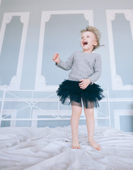 naughty little girl jumping on parent's bed.