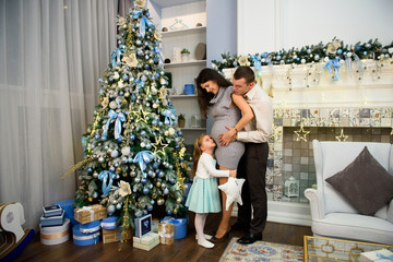 Christmas family standing near the Xmas tree. Living room decorated by Christmas tree and present gift box.